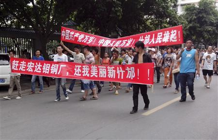Local residents march with banners during a protest along a street in Shifang, Sichuan province