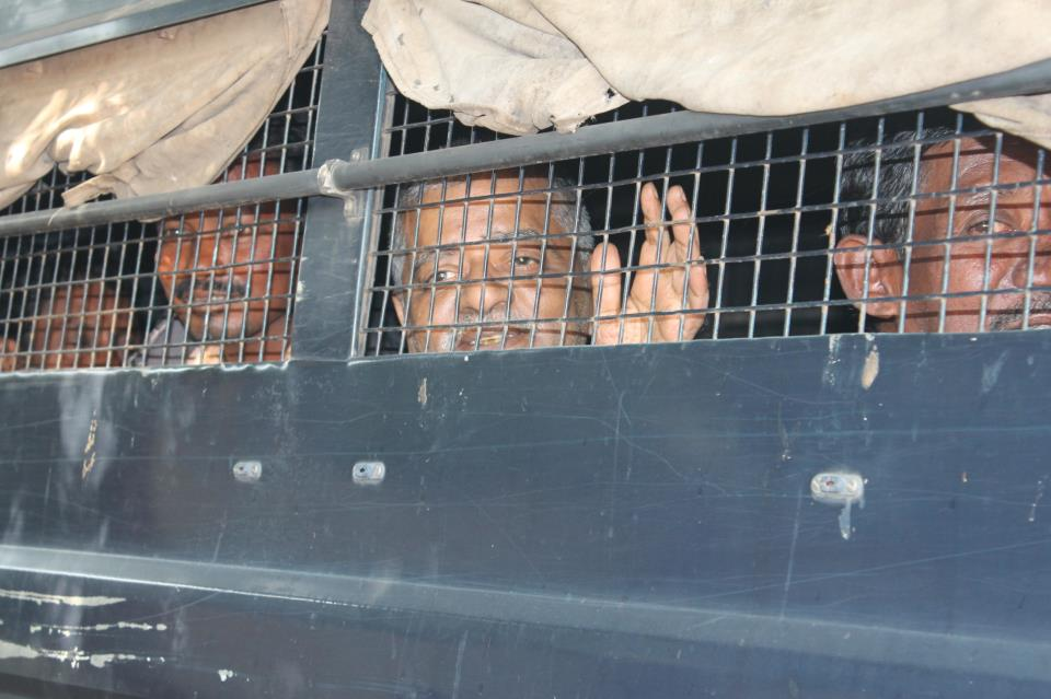 Xavier Dias (with hand raised) on way to prison