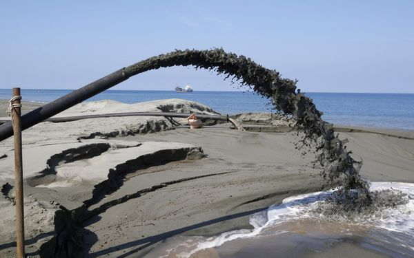 A pipe spews water mixed with waste black sand coming from a magnetized black sand mining equipment along the shore line of Ilocos Sur, in northern Philippines